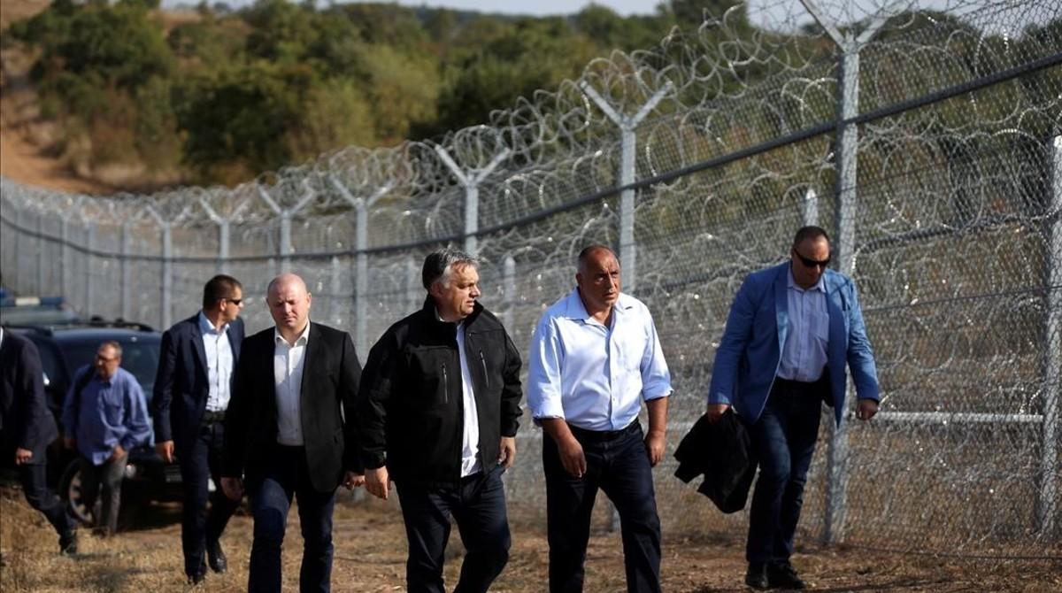 El primer ministro húngaro, Viktor Orbán (centro, con chaqueta negra) y su homólogo búlgaro, Boiko Borisov (derecha) inspeccionan la valla de alambradas construida en la frontera con Turquía, cerca de Lesovo (Bulgaria), el 14 de septiembre del 2016.