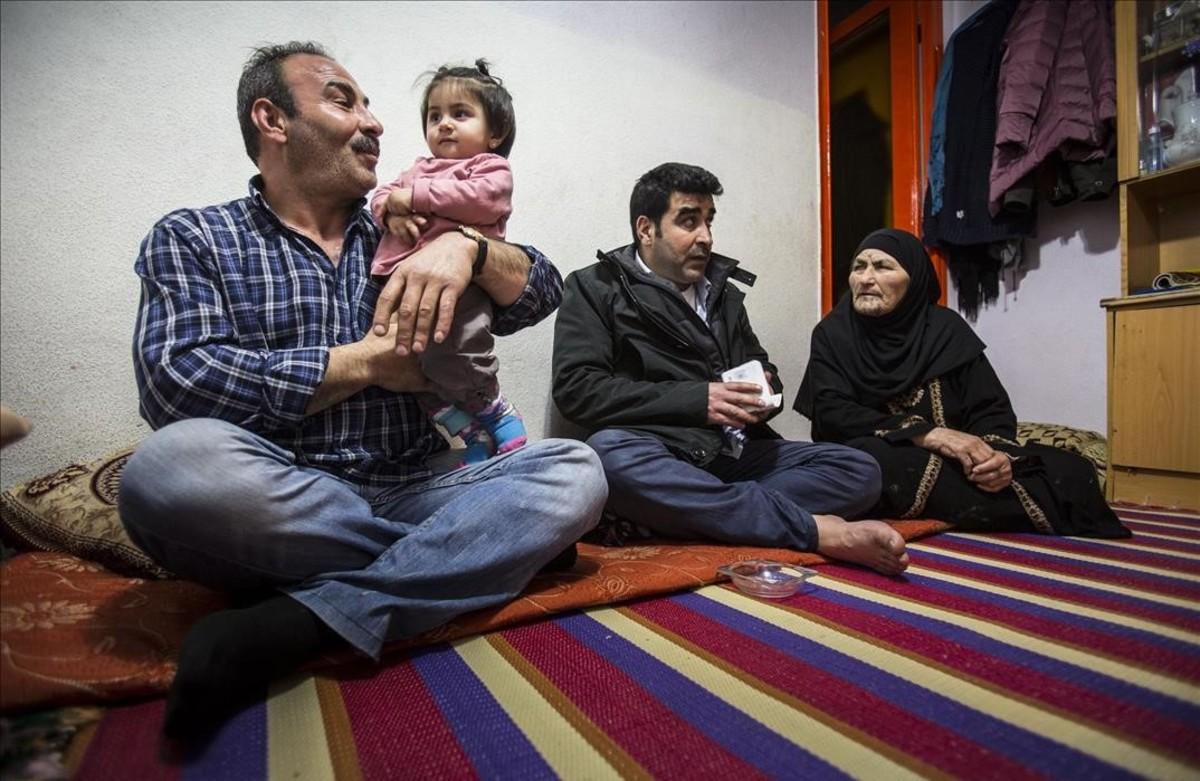 El refugiado sirio Walid, en primer término, juega con su nieta Hajar, nacida en Catalunya.