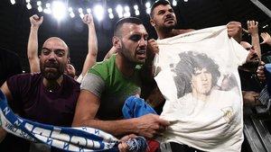 Seguidores del Nápoles celebran el final de un partido con una camiseta y la imagen de Maradona.