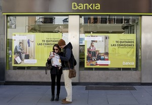 Tourists look at a city map in front of a Bankia bank branch in the Andalusian capital of Seville, southern Spain February 17, 2016. REUTERS/Marcelo del Pozo