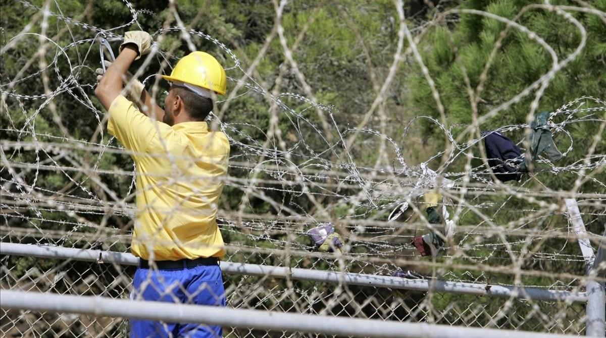 Un trabajador repara la barrera de alambradas de Melilla, tras un intento de inmigrantes africanos por superarla desde Marruecos, el 5 de octubre del 2005.