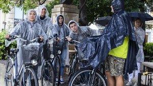 Un grupo de turistas trata de protegerse de la lluvia este jueves en el centro de València