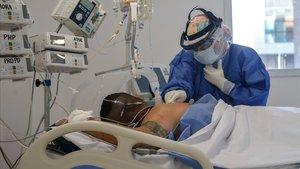 Una doctora controla el estado de un paciente ingresado en una uci.