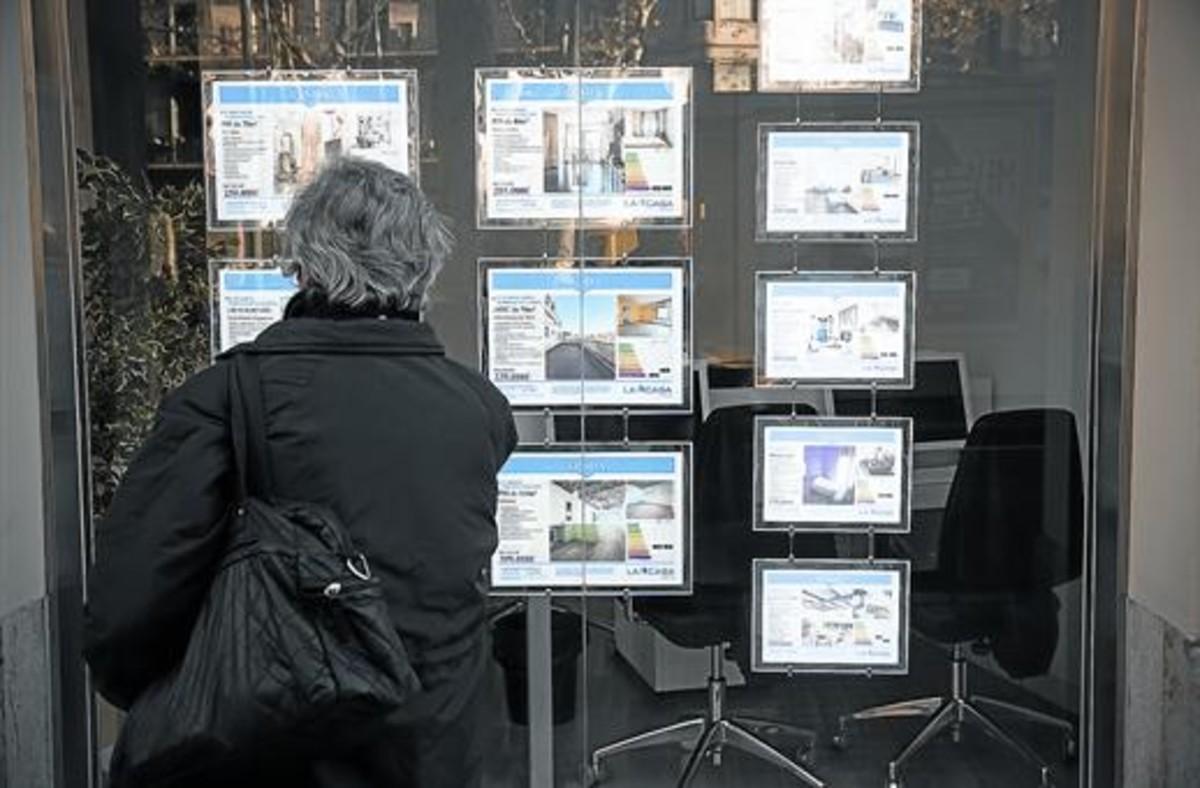 Una mujer consulta anuncios de pisos en una inmobiliaria de Barcelona.