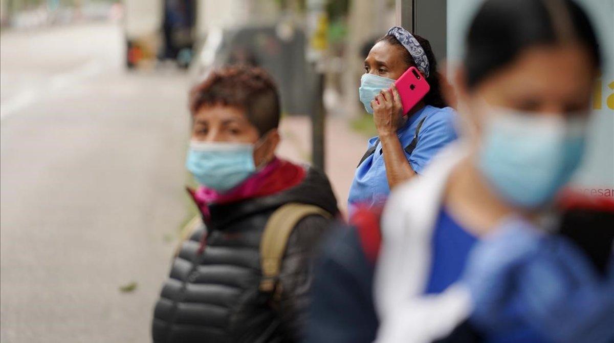 Varias personas hacen cola en la parada de un autobús, esta semana en Madrid.