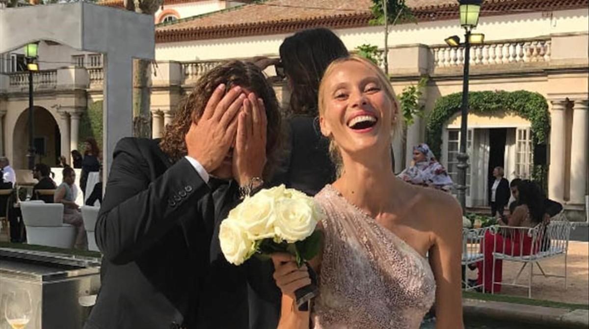 Carles Puyol bromea con su pareja, Vanesa Lorenzo, que posa con el ramo de novia de Yolanda Cardona.