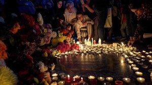 Personas depositan flores y velas en la plaza de Charles Aznavour, en Yerevan, la capital de Armenia.