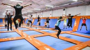 Un grupo de adultos saltan como niños sobre las camas elásticas deThe Indoor Jumping Club.