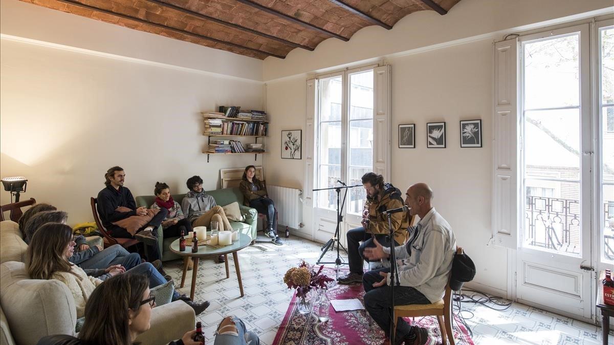 Iñaki Nazabal recita un poema con la guitarra de Ian Sala de fondo en la sala de estar de un piso de Gràcia.