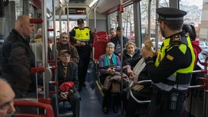David Vàzquez, a la derecha, jefe de la UIPA de la Guardia Urbana, da explicaciones a los jubilados en un autobús. A la izquierda, un instructor de TMB.
