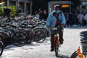 Un individuo con mascarilla circula en bicicleta por Wuhan.