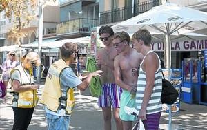 Un agente cívico pide a unos jóvenes en bañador que se pongan la camiseta, el verano pasado, en el paseo de Joan de Borbó, en la Barceloneta.