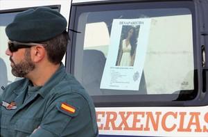 Un agente de la Guardia Civil, el 1 de septiembre, junto al cartel de búsqueda de Diana Quer, desaparecida en A Pobra do Caramiñal (A Coruña).