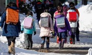 Alumnos de primaria se dirigen a su centro escolar en la ciudad japonesa de Sapporo.