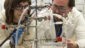 Los investigadores Álvaro Reyes y Marta Blasco, del ICIQ, observan el funcionamiento del nuevo catalizador para la obtención más barata del hidrógeno.