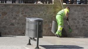 Un barrendero limpia una acera de la calle de Mallorca, en Barcelona.