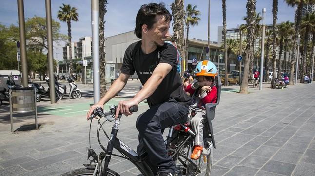 Un menor con casco, camino del colegio con su padre.