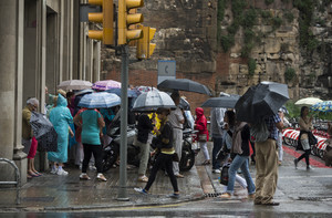 Diversos ciutadans es protegeixen de la pluja, aquest diumenge a Barcelona.