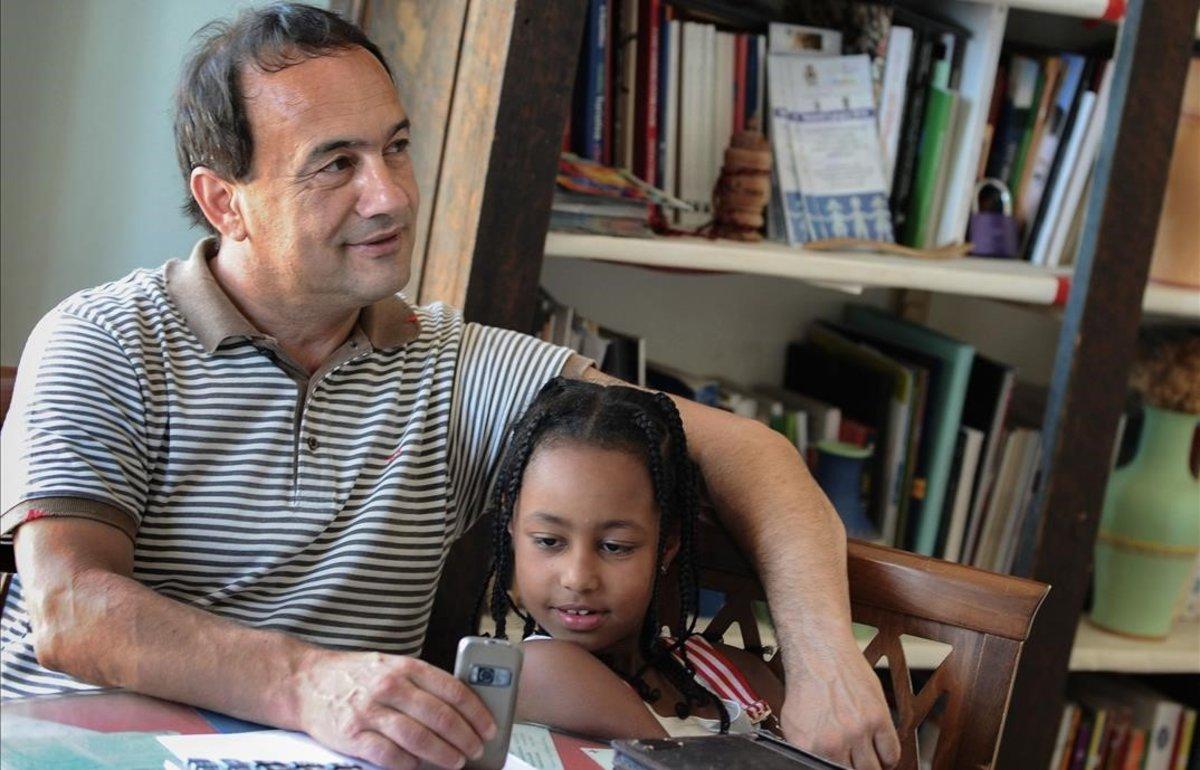 Domenico Lucano, exalcalde de Riace, posa con una niña etíope en una imagen del 2011.