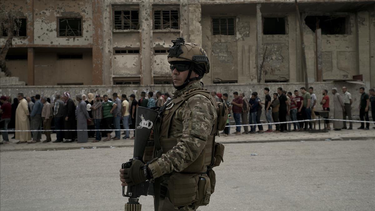 Un soldado iraquí vigila un centro electoral situado en un edificio semiderruido de Mosul.