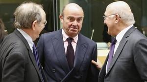 El ministro español en funciones de Economía,Luis de Guindos, conversa con el ministro italiano de Finanzas Pier Carlo Padoan y su homólogo francés Michel Sapin durante la reunión del Eurogrupo.