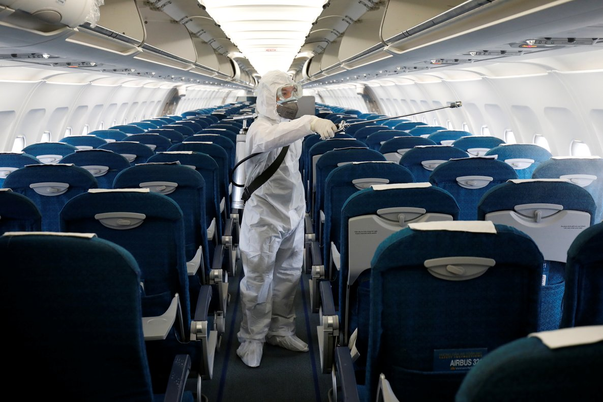 FILE PHOTO: A health worker sprays disinfectant inside a Vietnam Airlines airplane to protect against the recent coronavirus outbreak, at Noi Bai airport in Hanoi, Vietnam February 21, 2020. REUTERS/Kham/File photo
