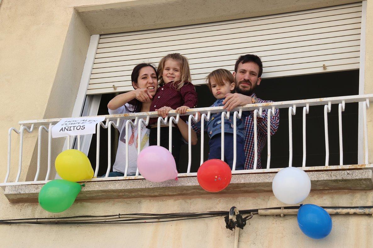 La familia deÀlex sale al balcón para que los vecinos le canten el 'cumpleaños feliz'.