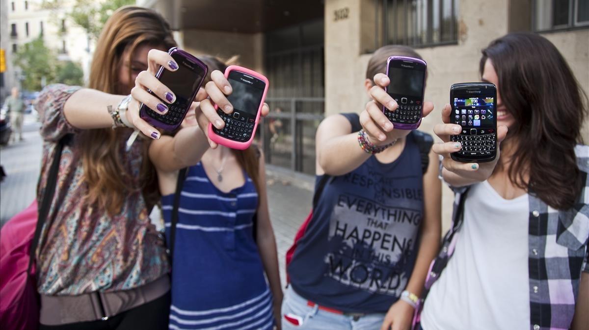 Tres adolescentes muestran sus teléfonos, en una imagen del 2011.