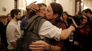 El líder de Podemos, Pablo Iglesias, y el de En Comú Podem, Xavier Domènech, celebran con un beso y un abrazo el primer paso hacia la derogación de la ley mordaza.