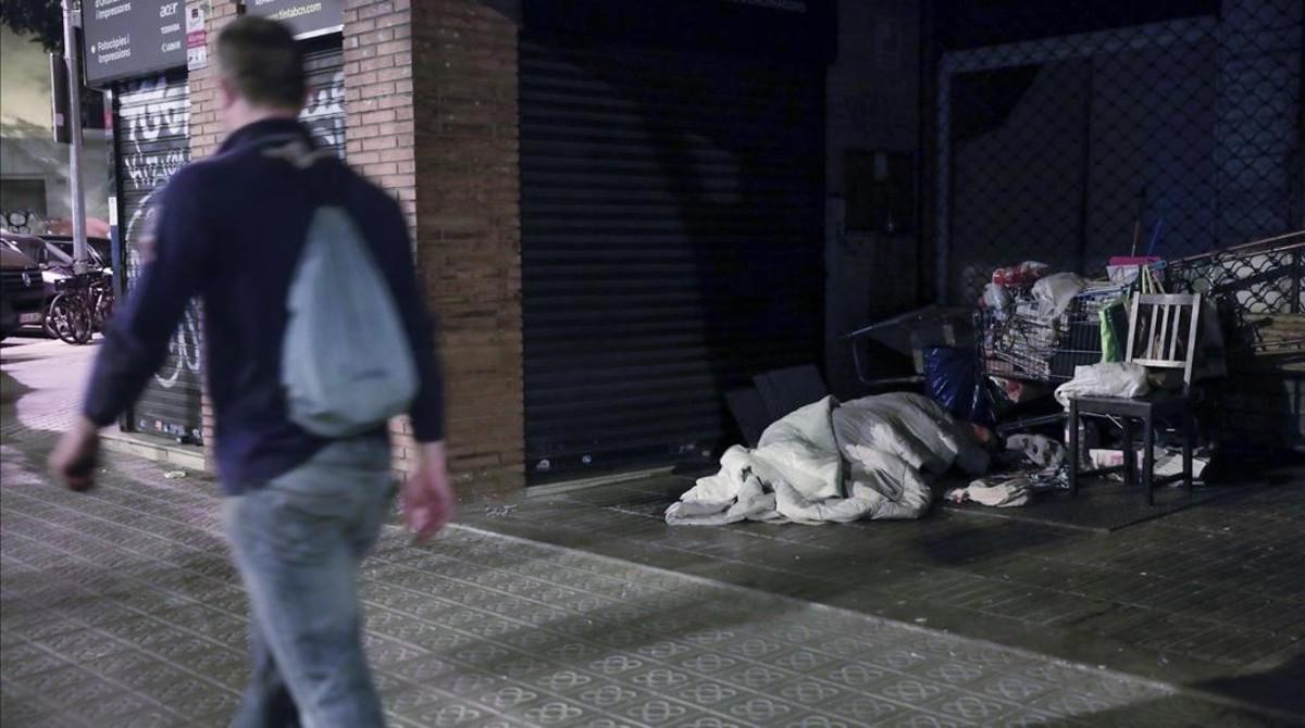 Una persona durmiendo en la calle, en el Eixample de Barcelona.