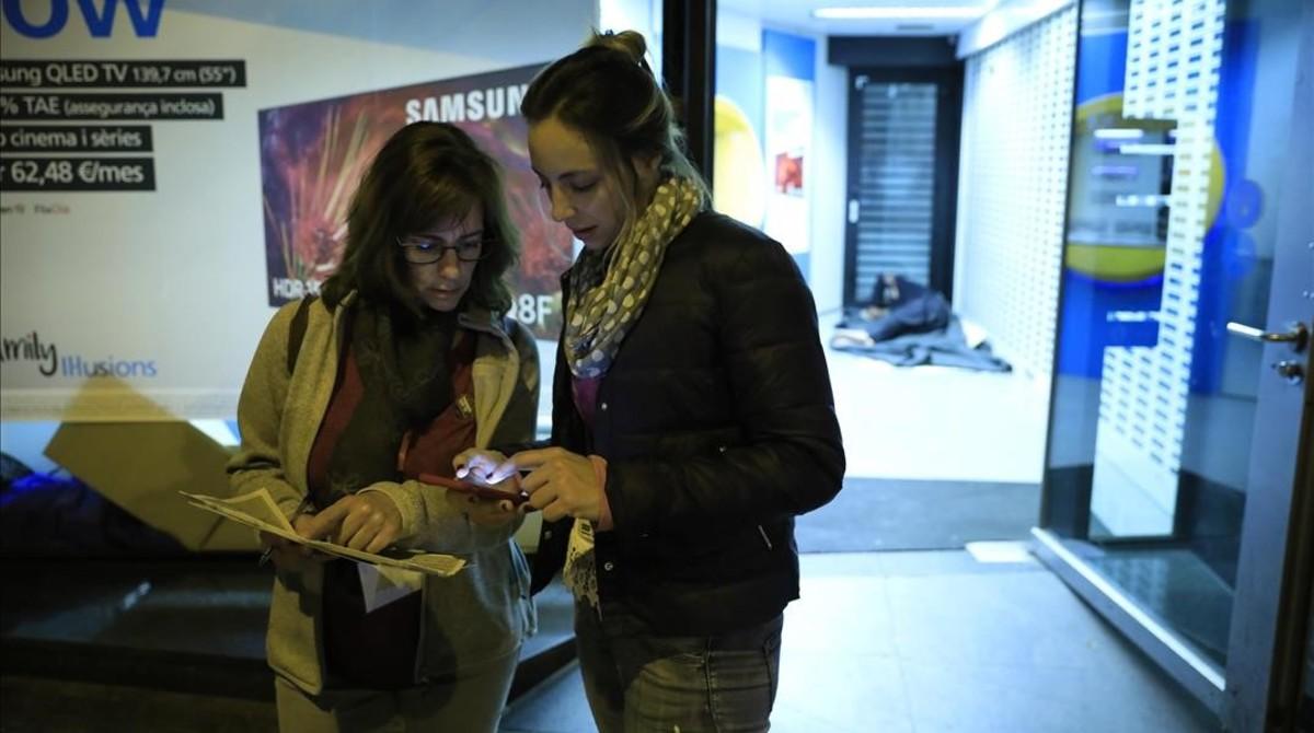 Las voluntarias Mónica Galcerány Alba López inscriben en su base da datos a un sintecho detectado en un cajero en L'Esquerra del Eixample, la pasada madrugada.