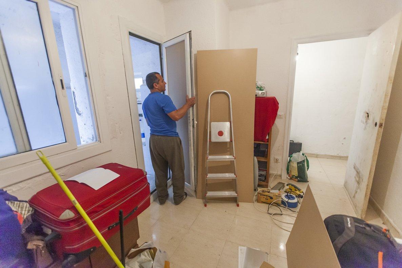 Juan Carlos coloca una de las 'nuevas' puertas en la habitación donde los hermanos guardan su ropa en maletas (a la izquierda).