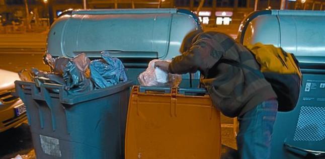 Una persona busca comida en un contenedor de desechos orgánicos.
