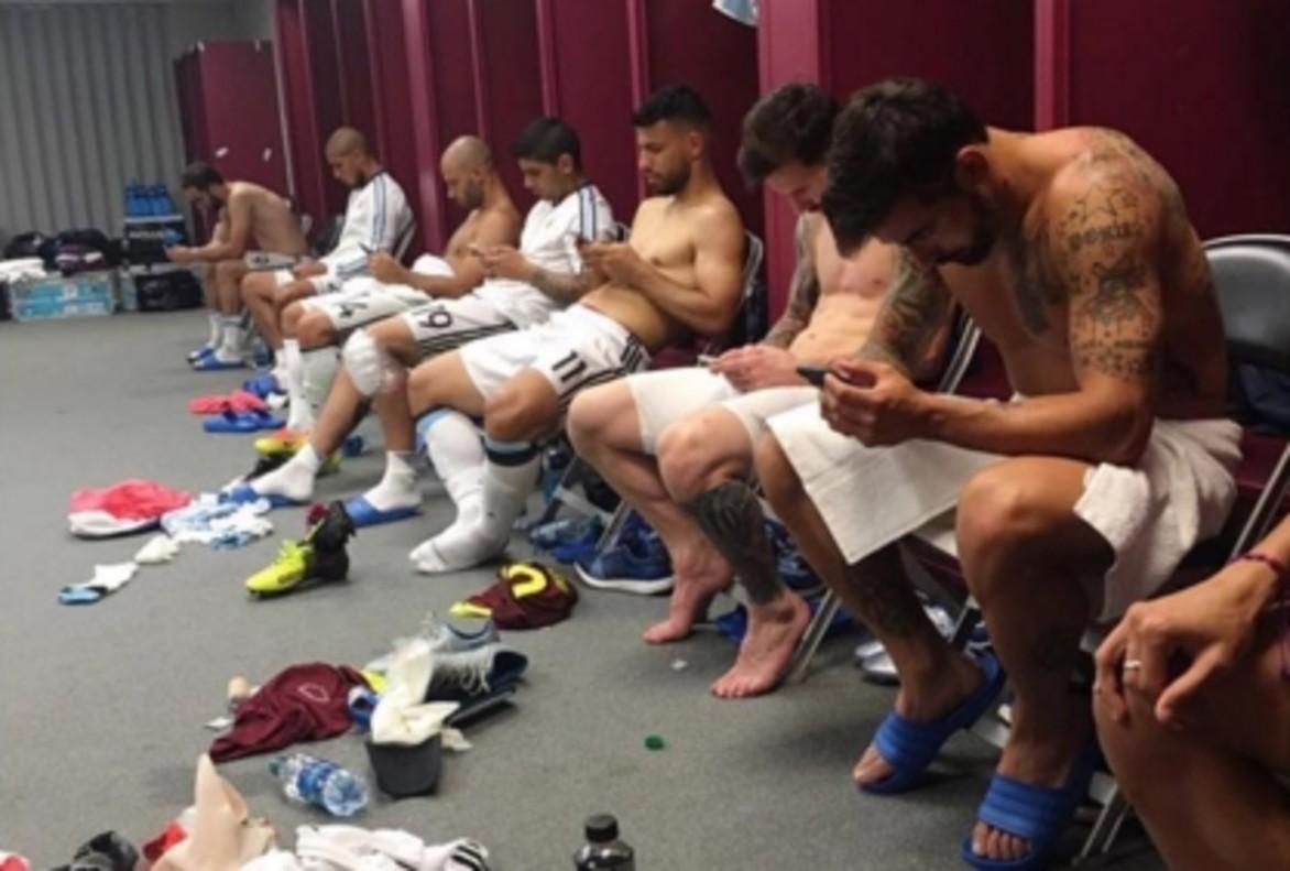 Los jugadores de Argentina, pendientes de sus teléfonos móviles tras la victoria sobre Venezuela.