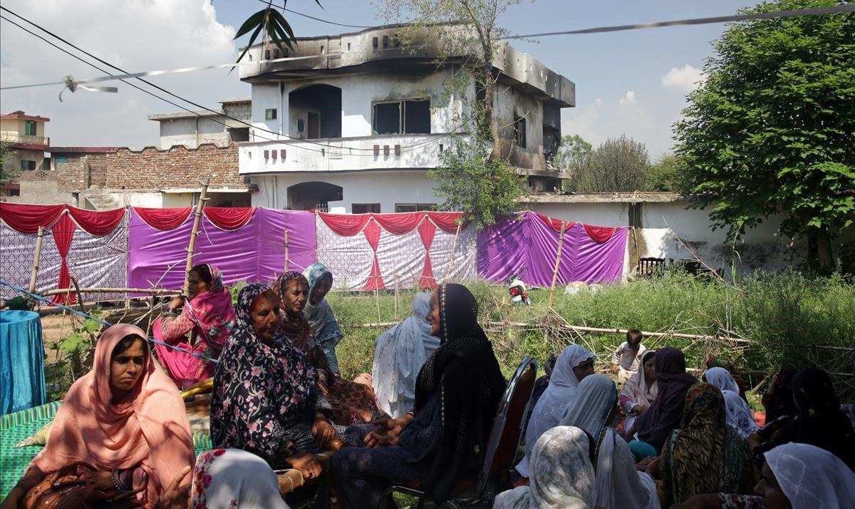 Mujeres y niños se sientan cerca de un edificio dañado con manchas de humo después de que un avión militar en un vuelo de entrenamiento se estrellara en un área urbanizada en la ciudad de la guarnición de Rawalpindi, Pakistán, 30 de julio de 2019
