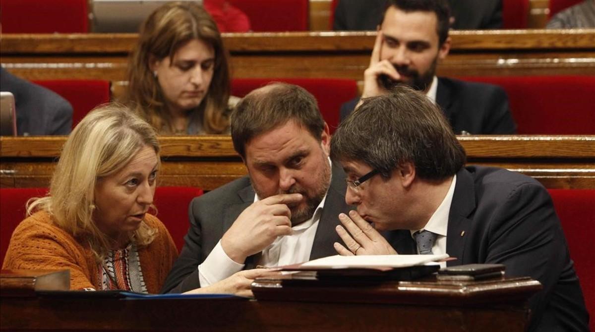 El 'president' Carles Puigdemont conversa con el vicepresidente Oriol Junqueras y la 'consellera' Neus Munté.
