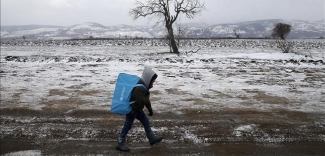 Un niño refugiado, con una mochila cargada, camina por un campo congelado en Serbia.