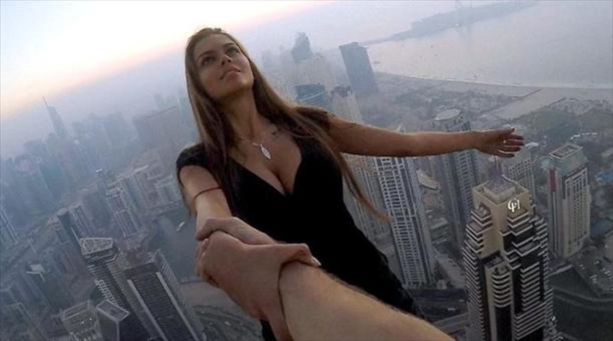 La modelo rusa Viki Odintcova, de la mano de su asistente, a 300 metros de altura.
