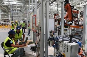 Operarios de la fábrica de Seat en Martorell, trabajando con brazos robotizados.