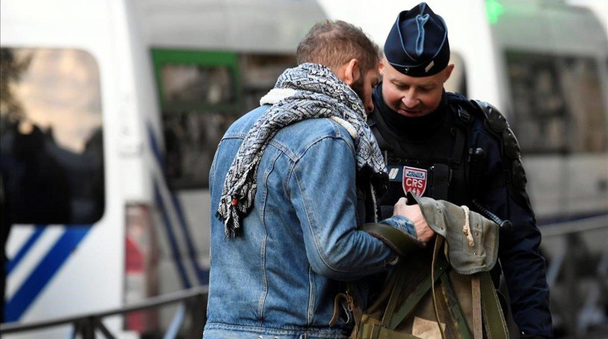 Un policía examina la mochila de un joven en París.