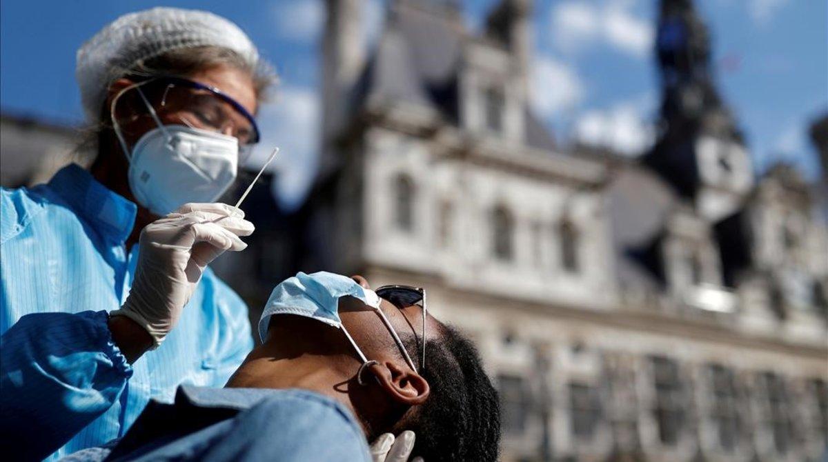 Un sanitario realiza una PCR frente al Ayuntamiento de París.