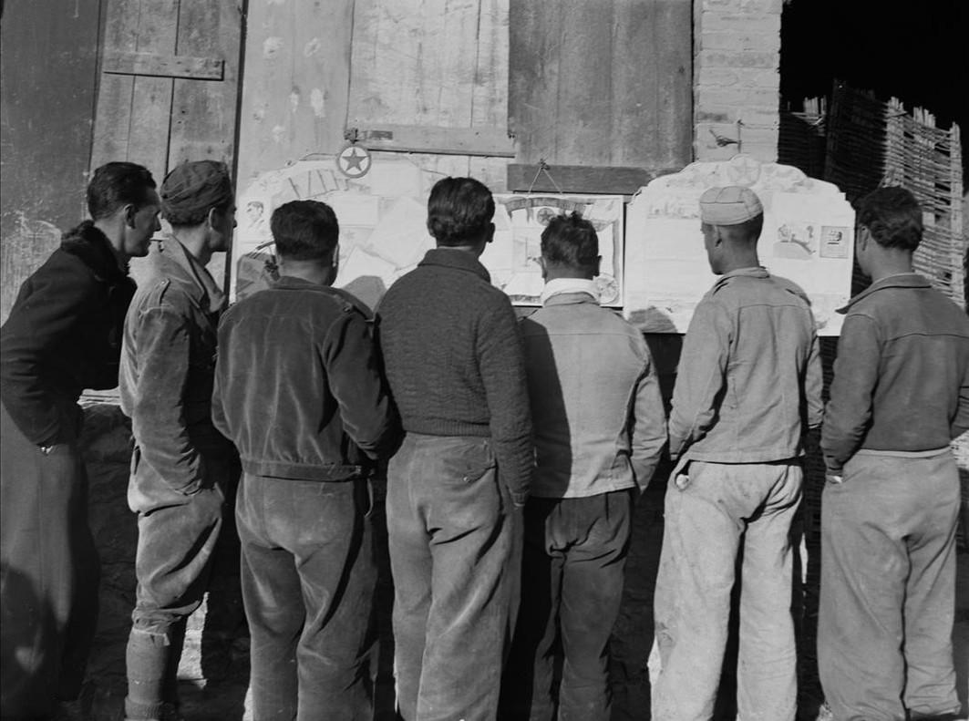 Soldados leyendo un periódico mural.