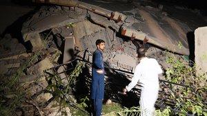 Habitantes de Mirpur observan uno de los edificios derrumbardos por el terremoto.