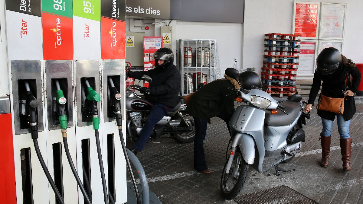 Una gasolinera con varios clientes repostando.
