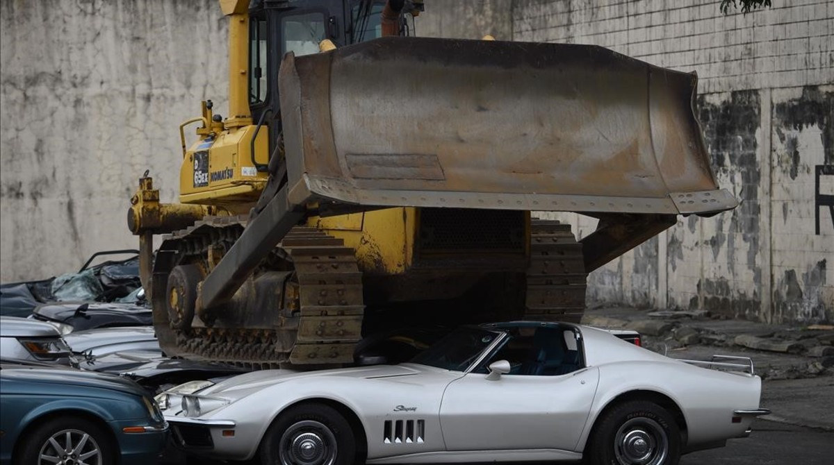 Un buldózeraplastando los coches en Manila.