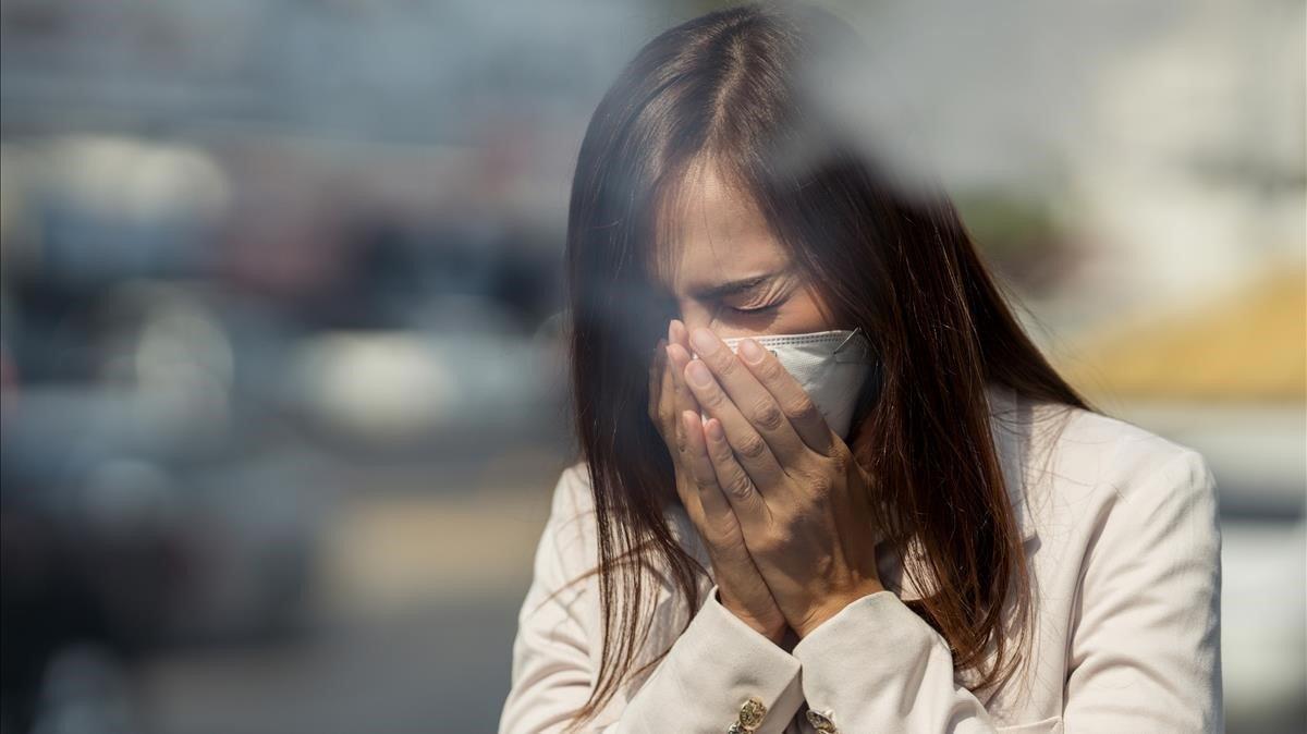 Una mujer estornuda mientras lleva puesta una mascarilla, el pasado 30 de julio.