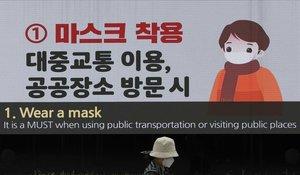 Una mujer pasa junto a una pantalla mostrando medidas de precaución par evitar la propagación del coronavirus, en Seúl, este domingo.