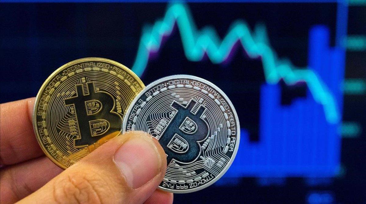 Una persona con dos representaciones físicas del Bitcoin.