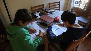 Unos niños haciendo deberes.
