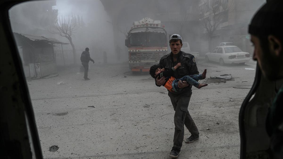 Un voluntario de los Cascos Blancos sirios lleva a un niño herido en brazos hasta una ambulancia, tras un bombardeo en Duma (Guta Oriental), el 22 de febrero.